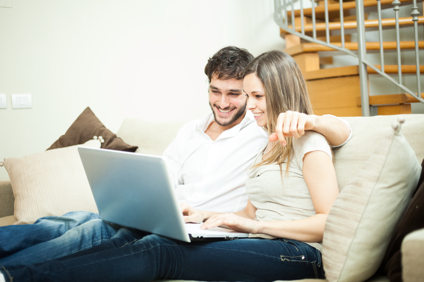 Couple using a notebook while relaxing on the couch